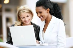 Interracial businesswomen working on laptop.