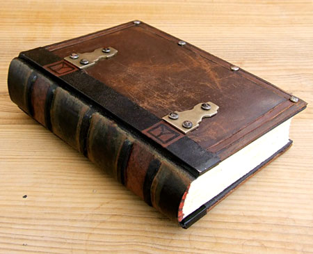 A brown journal with metal hinge accents